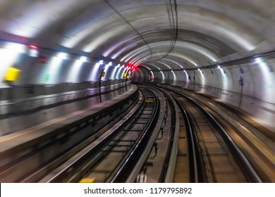 Riding the train in subway metro underground tube tunnel illuminated railroad track with motion blur effect