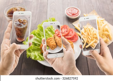 riends using smartphones to take photos of fried chicken and french fries and cola.