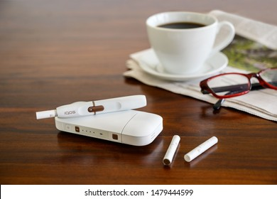 RIEPS, GERMANY, AUGUST 15, 2019: Iqos heating tobacco system, coffee cup and newspaper on a brown table, new e-cigarette with tobacco sticks for reduction in smokers, copy space, selected focus