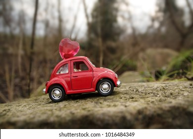 Rieps, Germany - February 1, 2018: red miniature car with a heart on the roof drives through a rocky forest landscape for valentines or mother's day with copy space, selected focus