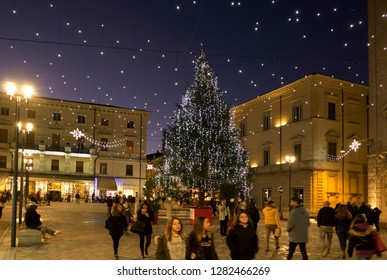 Rieti, Italy - 23 December 2018 - The historic center during Christmas holidays with lights decorations. View of central square, Christmas tree and people walking.