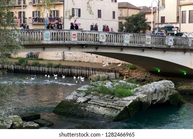 """Rieti, Italy - 23 December 2018 - The old and new """"Ponte Romano"""" bridges  with people walking over Velino river during Christmas holidays."""