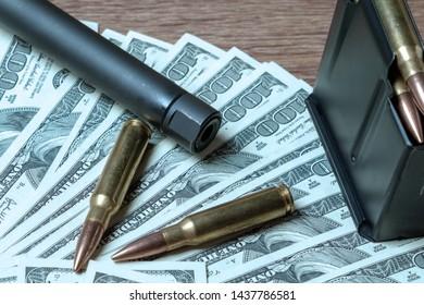 Rifle barrel, magazine and cartridges on money.