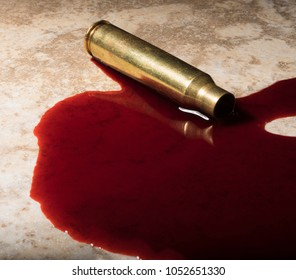 Rifle cartridge that has been shot in a bunch of blood on the floor