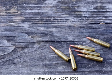 Rifle Cartridges arranged on the bottom right corner of wooden background