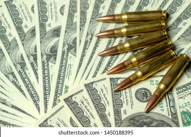 Rifle cartridges on dollars. Concept for crime, contract killing, paid assassin, war, global arms trade, weapons sale. Illegal hunting, poaching