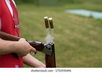 Rifle cartridges and smoke after firing. Man opens the shotgun bolt after  shot with smoke