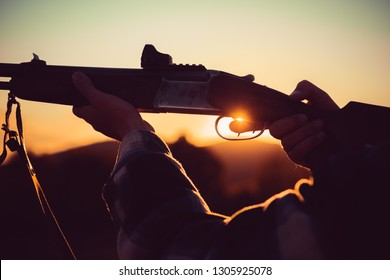 Rifle Hunter Silhouetted in Beautiful Sunset. Hunter with Powerful Rifle with Scope Spotting Animals. Pulled the trigger of the shotgun. Track down