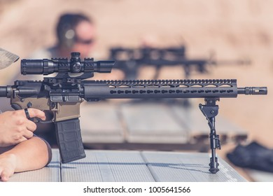 Rifle at the range with desert background man firing with black magazine