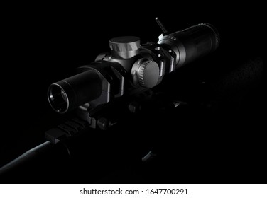Rifle scope mounted on a gun on a dark background