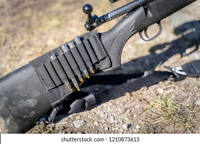 A Rifle Stock with Bullets on it and the Ground
