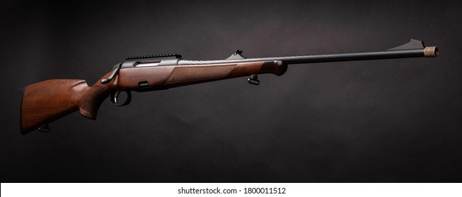 Rifle with a wooden stock on a dark background. Weapons for sports, hunting and self-defense.