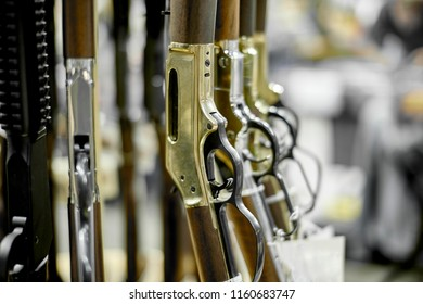 Rifles on a rack for sale with shallow depth of field