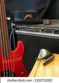 A musician's rig set on stage includes red fretless electric bass guitar, pork pie hat, amplifier, blues harmonicas and microphone.