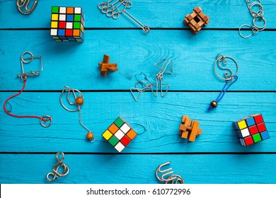 RIGA - 26 MARCH 2017: Wooden Brain Teaser and Rubik's Cubes on Blue Wooden Background, Top View