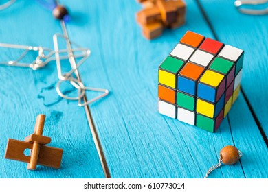 RIGA - 26 MARCH 2017: Wooden Brain Teaser and Rubik's Cube on Blue Wooden Background