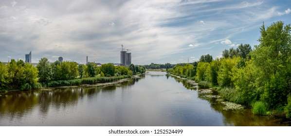 Riga city, capital of Latvia panoramic view with river Daugava and cable bridge with calm water in summer