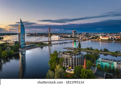 Riga city panorama with colorful sunset in the sky. Modern architecture meets old town. Picturesque view over riverside.
