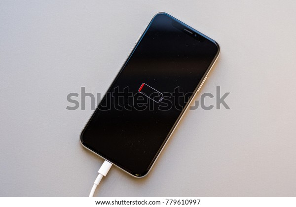RIGA, DECEMBER 19, 2017  - New Apple iPhone X is displayed with very low battery power indicator while attached to charging cable. Shallow focus effect. For editorial purposes.