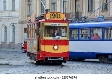 RIGA LATVIA 09 17 2015: Every Friday, Saturday, Sunday and holiday days, a restored tourist tram originally built in 1901 cruises Riga's streets. In front of the Latvian National Theater.