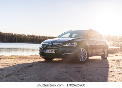 Riga, Latvia 10 April 2020 SKODA SUPERB COMBI B8 TYP 3V estate wagon combi family car, Stands by river lake sunset mood with sun flares. Front and side close up view to Škoda