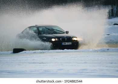 Riga, Latvia 10 february 2021 - car rides on water or ice, spray from the car. Front view