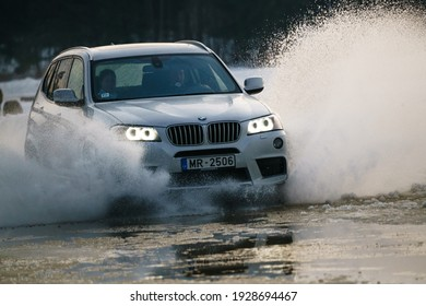 Riga, Latvia 10 february 2021 - bmw rides on water, spray from the car. Front view.
