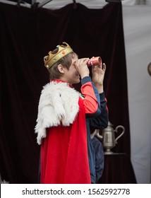 Riga, Latvia - 11.05.2019 Boy king with spyglass