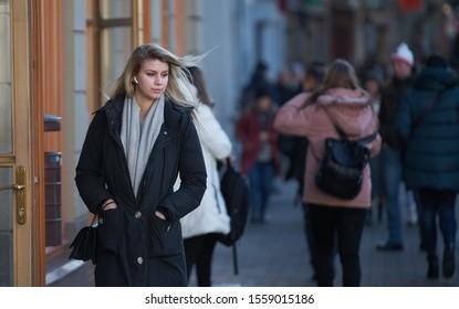 Riga, Latvia - 16.02.2019 People at Riga Streets. Blonde girl with headphones in black coat