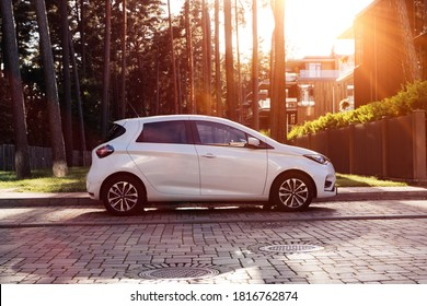 Riga Latvia 17 September 2020 Renault Zoe is a five-door supermini city electric car. Stands on parking lot in modern village private houses. Sunset mood lense flares