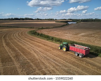 Riga, Latvia - 17.08.2019 Farmers works in field. Tractor. Aerial view.