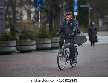 Riga, Latvia - 17.11.2018 man with bag on bicycle in Riga