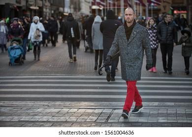 Riga, Latvia - 17.11.2018 man on crosswalk in Riga. Man with umbrella