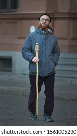 Riga, Latvia - 17.11.2018  Man in round glasses holding  torch in hand