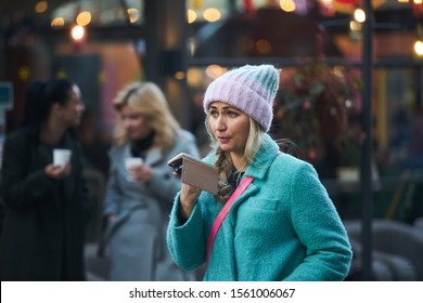 Riga, Latvia - 17.11.2018 woman in hat with phone in hands