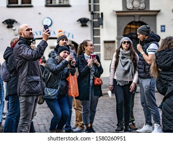 Riga, Latvia - 2019 Group of european tourists watching landmark at the street with luggage