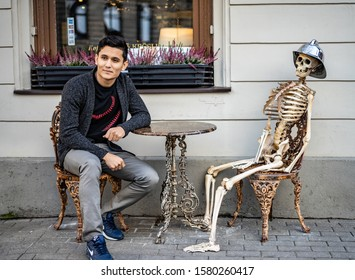 Riga, Latvia - 2019 skeleton and man behind coffee table at street