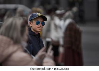 Riga, Latvia - 2019 The young man in blue shir and nice sunglasses looking at phone