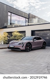 Riga, Latvia 21 July 2021, Porsche Taycan 4S Cross Turismo in Frozen Berry color. Car stand by modern private house at background. Car view from front and side at sunset time.
