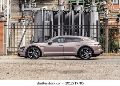 Riga, Latvia 21 July 2021, Porsche Taycan 4S Cross Turismo in Frozen Berry color. Car stand by power station at background. Car view from rear and side.