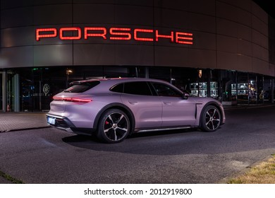 Riga, Latvia 21 July 2021, Porsche Taycan 4S Cross Turismo in Frozen Berry color. Car stand by entrance to Porsche shop background. Car view from rear and side at night time city.