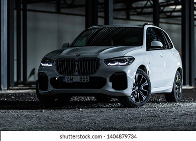 Riga, Latvia 22 May 2019- Bmw X5 M  package G05 in withe color. Stands in industrial location cargo containers storage in port freight.Dark room inside. Most popular SUV in the world. Front View.