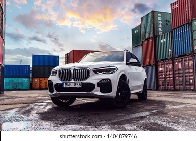 Riga, Latvia 22 May 2019- Bmw X5 M  package G05 in withe color. Stands in industrial location between cargo containers storage in port freight. Most popular SUV in the world. Sunset mood.