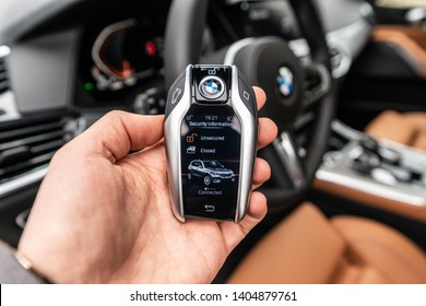 Riga, Latvia 22 May 2019- Bmw X5 M  package G05 in withe color. Close up view to New BMW X5M digital key in hand, car interior on background.