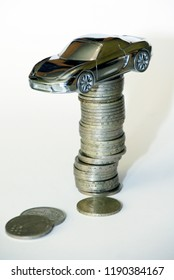 Riga, Latvia, 29.08.2018 Toy car on a money tower, symbolized car loan and Insurance, on white background