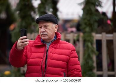 Riga, LAtvia  - 31.12.2018 Riga, Latvia. Old man look to the phone. man looking mobile screen