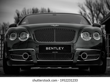 Riga, Latvia - 4 mart 2021: Bentley Continental GT Coupe tuning sport-car. It colored in black color. Editorial photo. Front view.