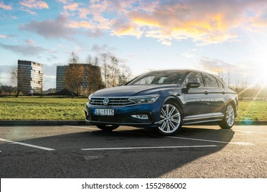 Riga, Latvia 7 November 2019 Volkswagen Passat (B8) facelift 2020, stands by park, car front and side view, background modern house and  building summer time lense flare