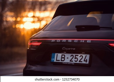 Riga, Latvia 8 December 2018, Porsche Cayenne (third generation) stand on countryside road, beautiful sunset colors close up view of back lights