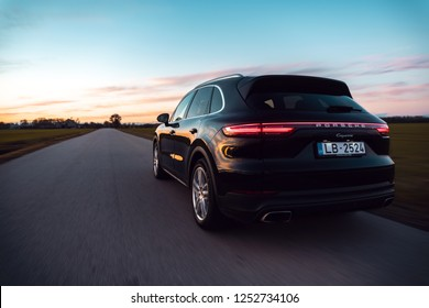 Riga, Latvia 8 December 2018, Porsche Cayenne (third generation) driving on countryside single road, beautiful sunset colors